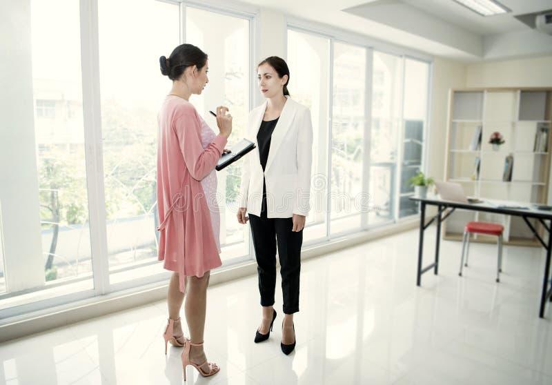 Affärskvinnor som talar om arbete, medan möta i regeringsställning företaget royaltyfri fotografi