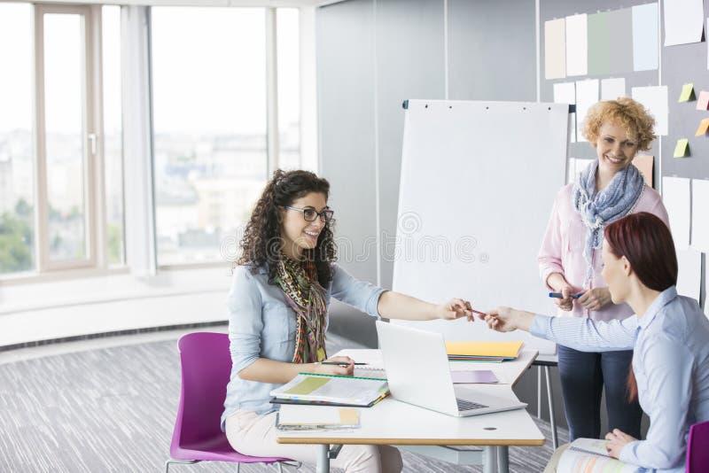Affärskvinnor som tillsammans arbetar i idérikt kontor arkivfoto