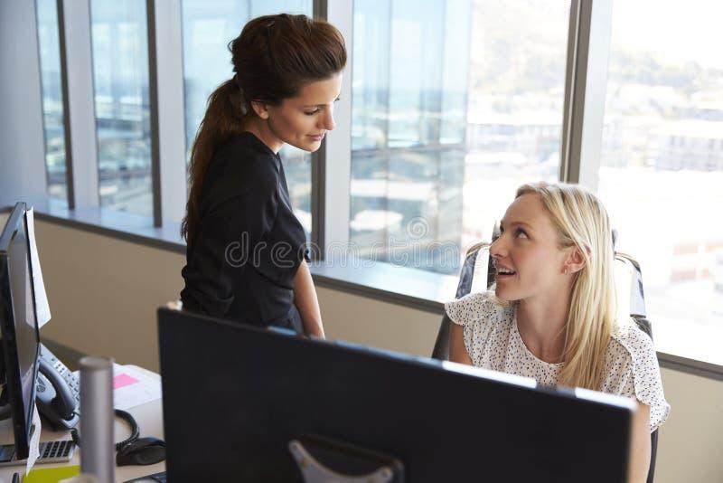 Affärskvinnor som tillsammans arbetar på kontorsskrivbordet på datoren royaltyfri bild