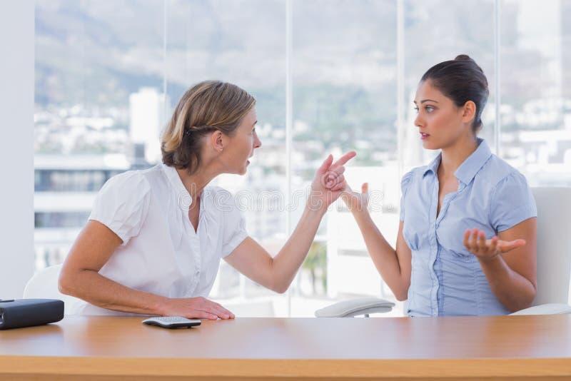 Affärskvinnor som tillsammans argumenterar royaltyfri foto