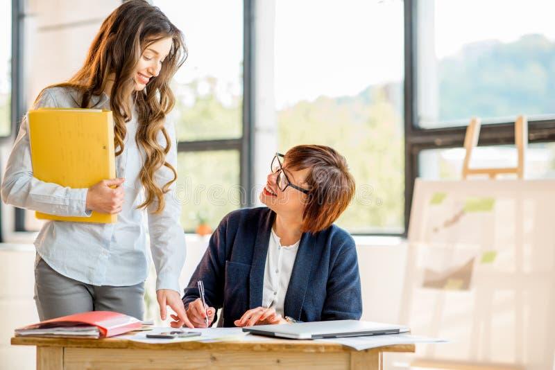 Affärskvinnor som tillsammans inomhus arbetar arkivbild