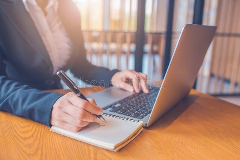 Affärskvinnor tar anmärkningar på papper med en svart penna, och hon använder en bärbar datordator på ett träskrivbord i kontoret royaltyfri foto