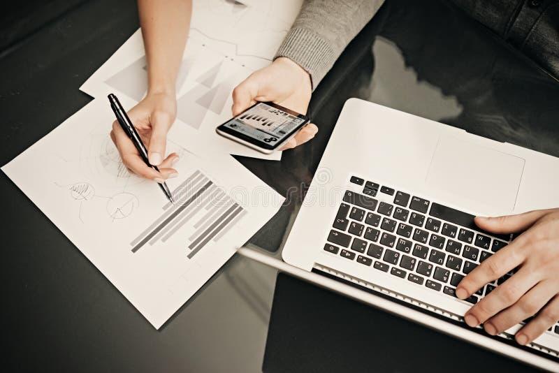 Affärsläge, lagarbetsprocess Penna för kvinnlig hand för foto hållande Mannen som använder smartphonen och den moderna bärbara da royaltyfria bilder