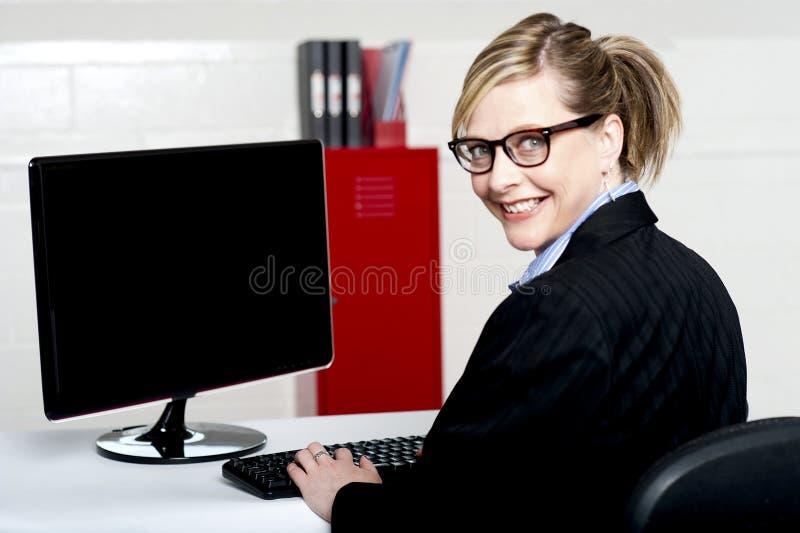 Affärslady som baksidt vänder och ler på kameran arkivfoton