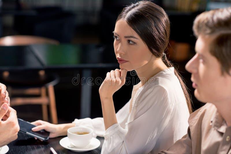 Affärslag på möte som diskuterar projekt i kafé royaltyfri foto