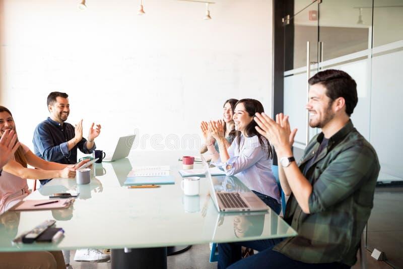 Affärslag som applåderar efter ett möte arkivfoto