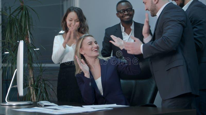 Affärslag som applåderar under möte i kontoret royaltyfria foton