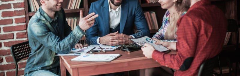Affärslag som diskuterar en finansiell rapport på den pro-företags`en s arkivfoto