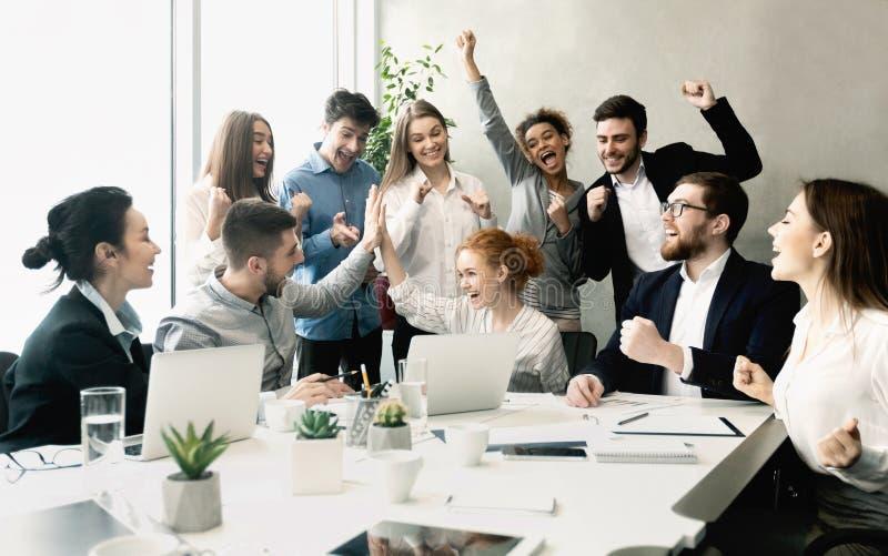 Affärslag som firar framgång tillsammans på arbetsplats royaltyfri fotografi