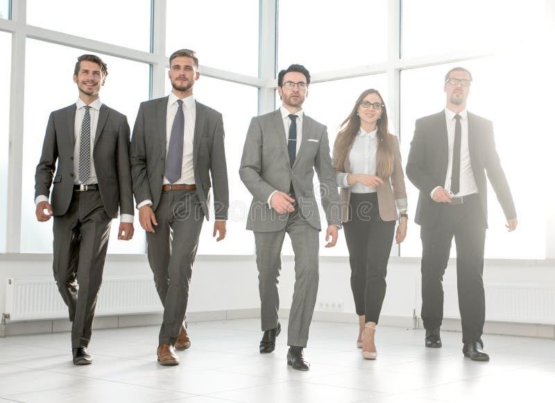 Affärslag som går på den moderna kontorsinre arkivfoto