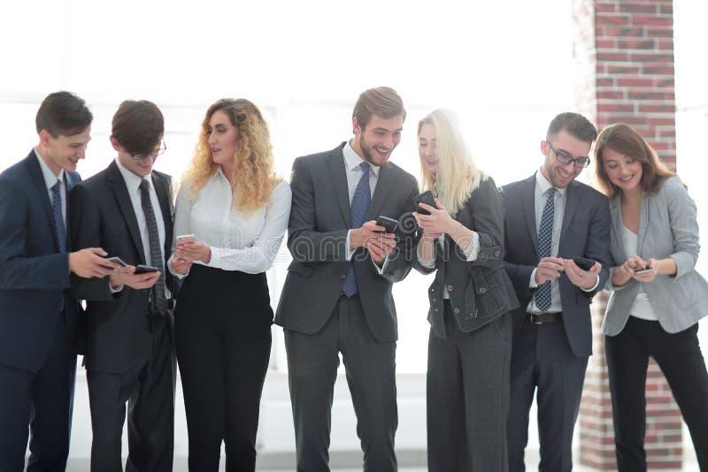 Affärslag som i regeringsställning ser till smartphonen fotografering för bildbyråer