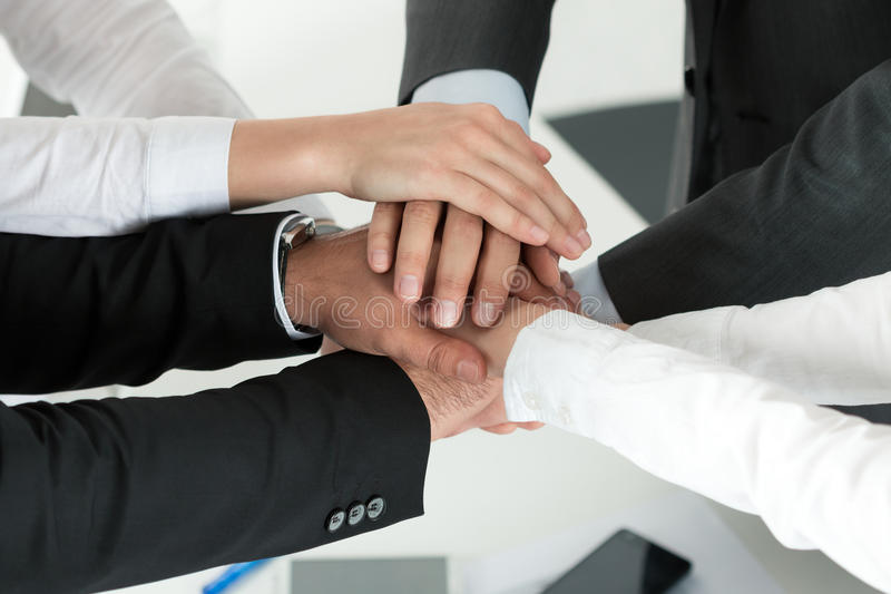 Affärslag som visar enhet med att sätta deras händer tillsammans royaltyfri fotografi
