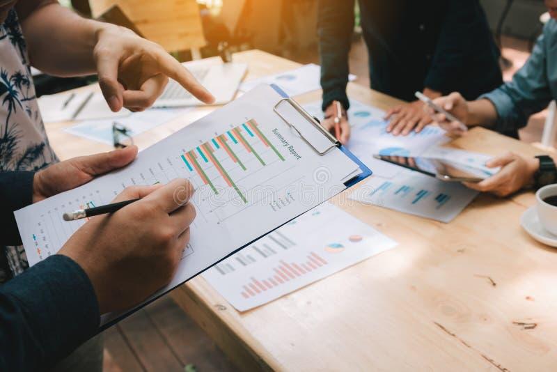Affärslagdiskussion om kostnadsföretaget som tillsammans arbetar och pekar den pappers- summariska grafen arkivfoto
