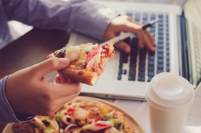 Affärslaget äter pizza på arbete, medan arbeta royaltyfri bild
