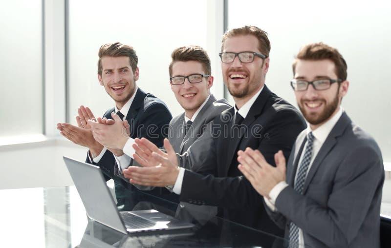 Affärslaget applåderar att sitta på skrivbordet royaltyfri fotografi