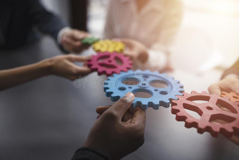 Affärslaget förbinder stycken av kugghjul Teamwork-, partnerskap- och integrationsbegrepp fotografering för bildbyråer