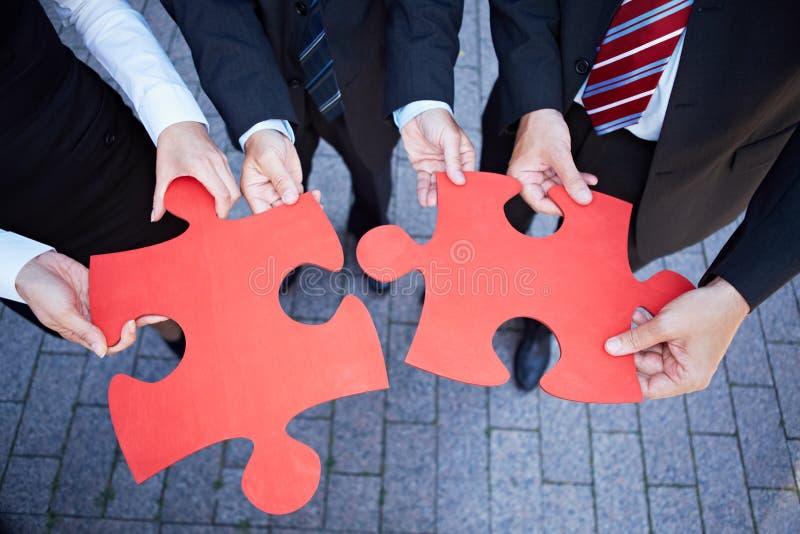 Affärslaget hands holdingjigsawen royaltyfri bild