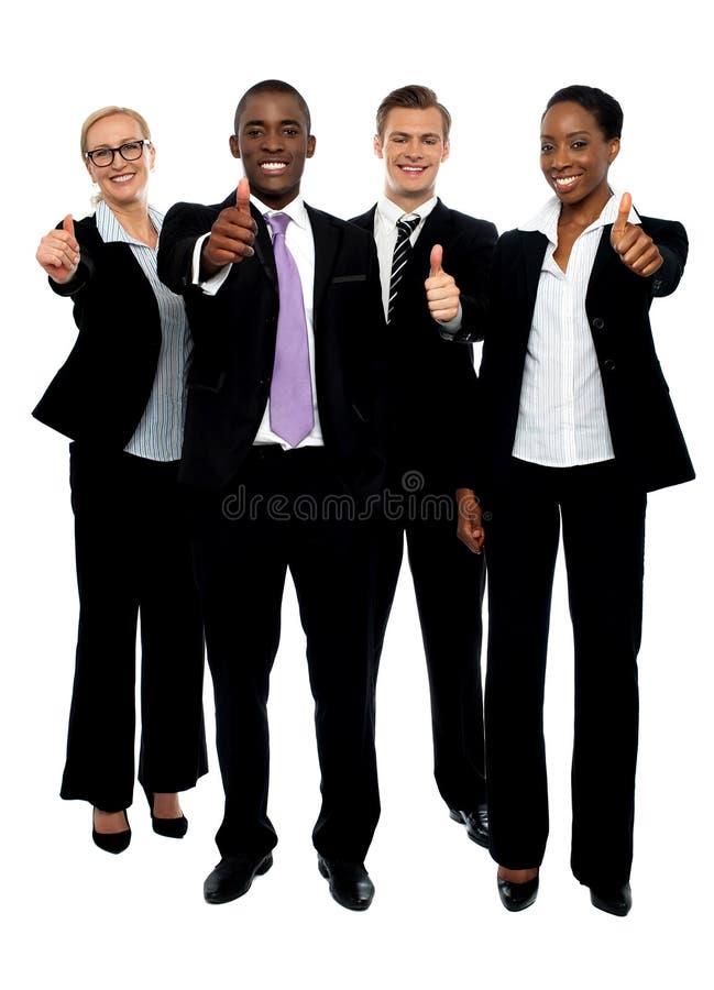 Affärslagfolket grupperar upp göra en gest tum royaltyfri foto