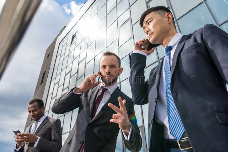 Affärslagmöte och användasmartphones utomhus nära kontorsbyggnad royaltyfri fotografi