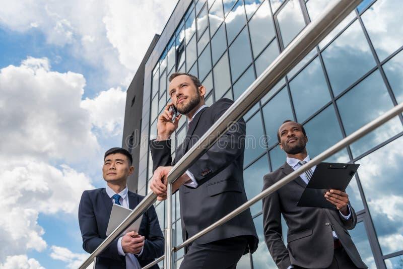 Affärslagmöte och för använda smartphone och digital minnestavla utomhus nära kontorsbyggnad arkivfoton