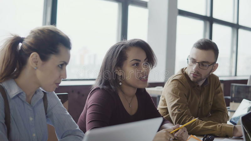 Affärslagmöte på det moderna kontoret Idérik ung grupp människor för blandat lopp som diskuterar nya idéer med chefen fotografering för bildbyråer