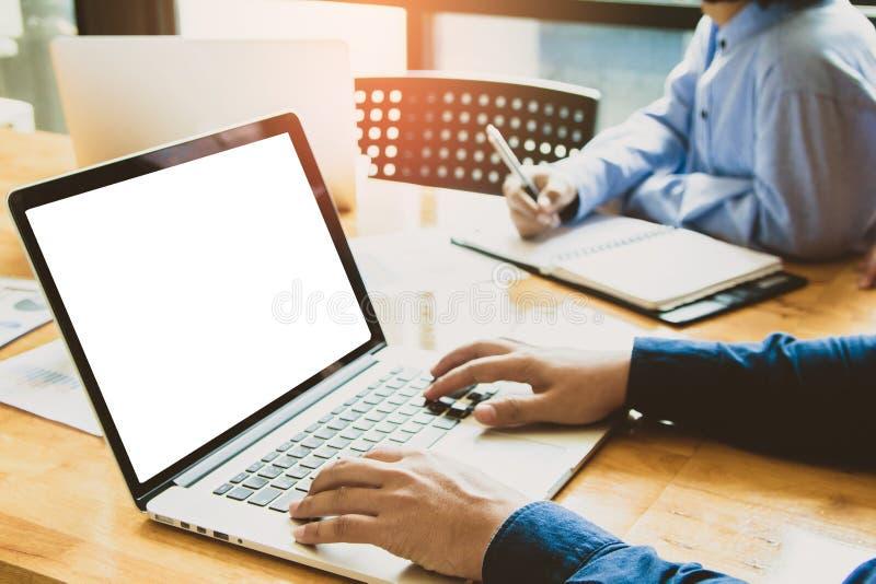 Affärslagmöte som arbetar på den digital bärbara datorn och punkt för att diskutera grafen upp och ner av ekonomi arkivbilder