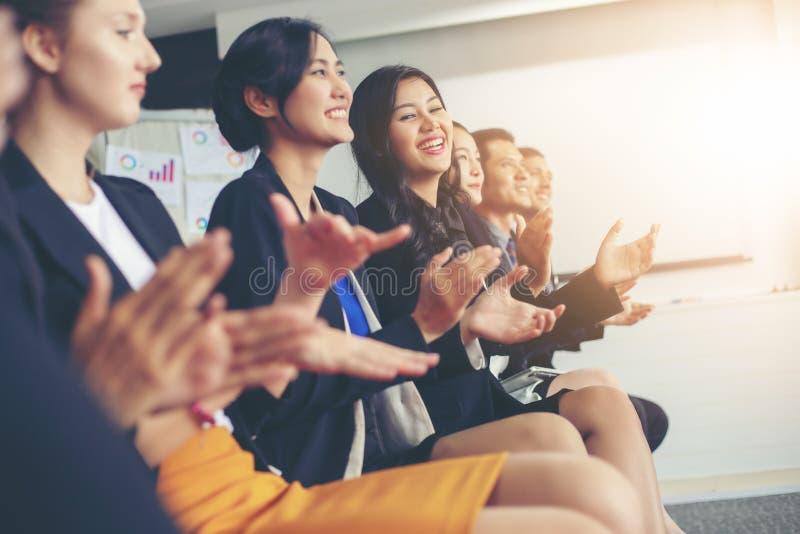 Affärsledare som applåderar i ett affärsmöte arkivfoto