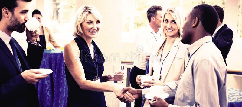 Affärsledare som påverkar varandra med de, medan ha kaffe royaltyfri foto