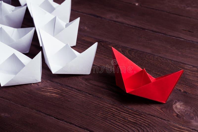 Affärsledarskapbegrepp med pappers- fartyg för vit och för färg på royaltyfria foton