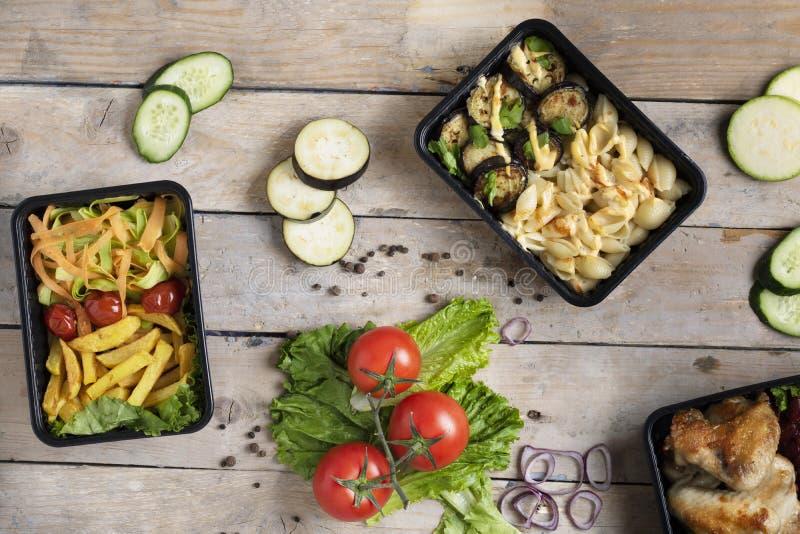 Affärslunch i mataskar, stekhönavingar, ångade grönsaker, kokt kött, klart mål som ska ätas royaltyfri bild