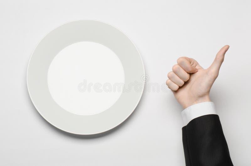 Affärslunch och sunt mattema: mannens hand i en svart dräkt som rymmer ett vitt, tömmer plattan, och shower fingrar gest på en is royaltyfria bilder