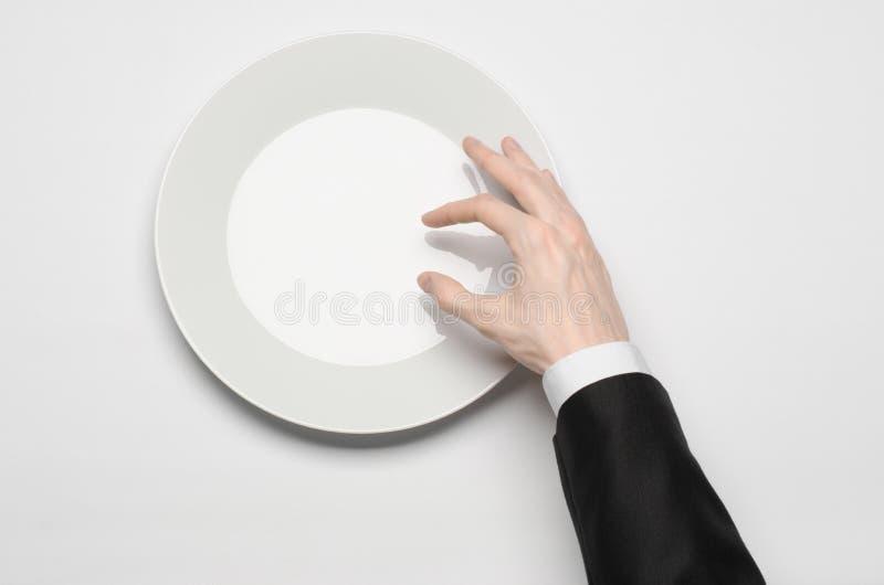 Affärslunch och sunt mattema: mannens hand i en svart dräkt som rymmer ett vitt, tömmer plattan, och shower fingrar gest på en is fotografering för bildbyråer