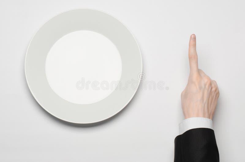 Affärslunch och sunt mattema: mannens hand i en svart dräkt som rymmer ett vitt, tömmer plattan, och shower fingrar gest på en is arkivbilder