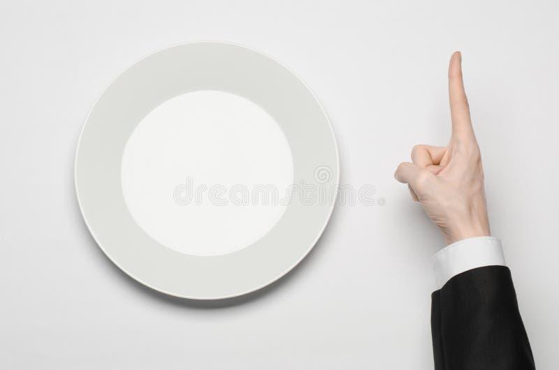 Affärslunch och sunt mattema: mannens hand i en svart dräkt som rymmer ett vitt, tömmer plattan, och shower fingrar gest på en is arkivfoto