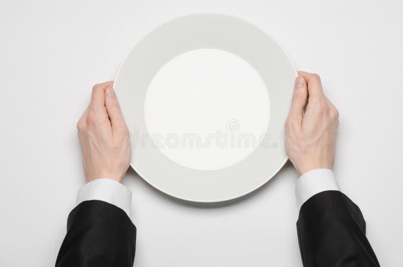 Affärslunch och sunt mattema: mannens hand i en svart dräkt som rymmer ett vitt, tömmer plattan, och shower fingrar gest på en is arkivbild