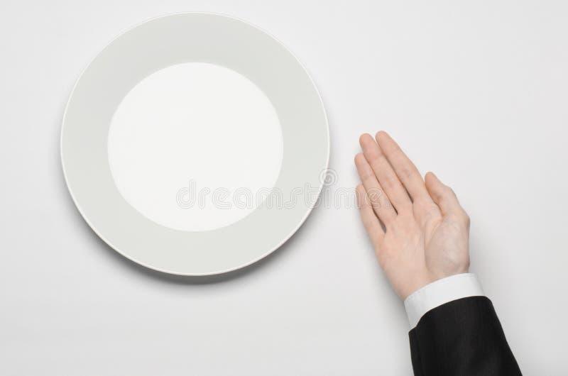 Affärslunch och sunt mattema: mannens hand i en svart dräkt som rymmer ett vitt, tömmer plattan, och shower fingrar gest på en is royaltyfri foto