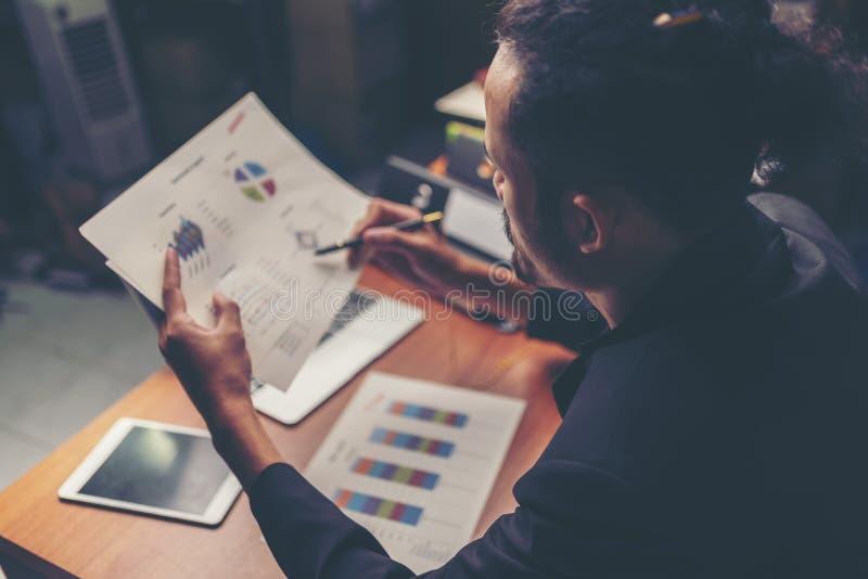 Affärsmän är analyserade data från rapport genom att använda smartphonen och l arkivfoton