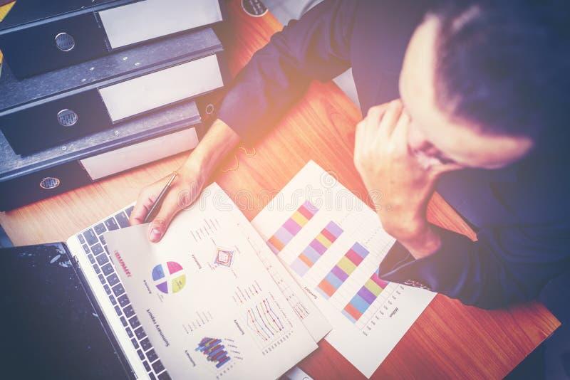 Affärsmän är analyserade data från rapport genom att använda smartphonen och l arkivbilder