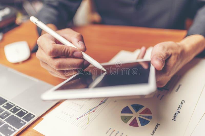 Affärsmän är analyserade data från rapport genom att använda smartphonen och l royaltyfria bilder