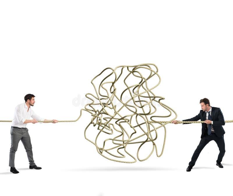 Affärsmän försöker att lösa ett tilltrasslat rep Begrepp av partnerskap royaltyfri bild