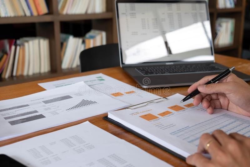 Affärsmän finans, redovisande arbete, checkräkningskonton och genom att använda räknemaskiner och finna information royaltyfria bilder