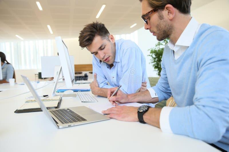Affärsmän i arbetsmöte med bärbara datorn royaltyfria foton