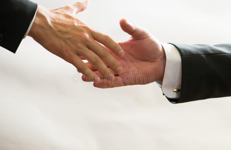 Affärsmän i dräkter når ut till varandra för handskakning, hjälper, handlar, finansierar fotografering för bildbyråer