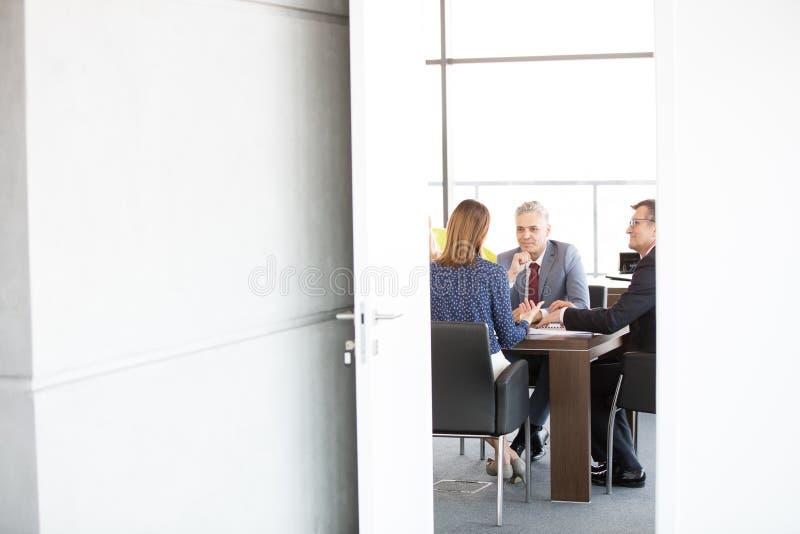 Affärsmän och affärskvinna i bräderum som ses till och med öppen dörr på kontoret royaltyfri bild