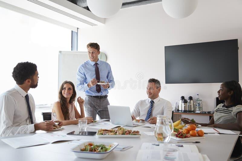 Affärsmän och affärskvinnor som möter i modern styrelse över arbetelunch royaltyfri fotografi