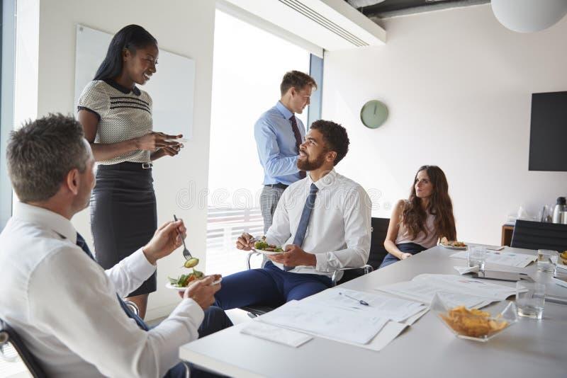 Affärsmän och affärskvinnor som möter i modern styrelse över arbetelunch royaltyfri foto