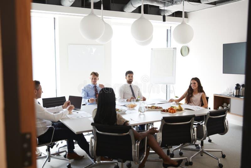 Affärsmän och affärskvinnor som möter i modern styrelse över arbetelunch royaltyfria foton