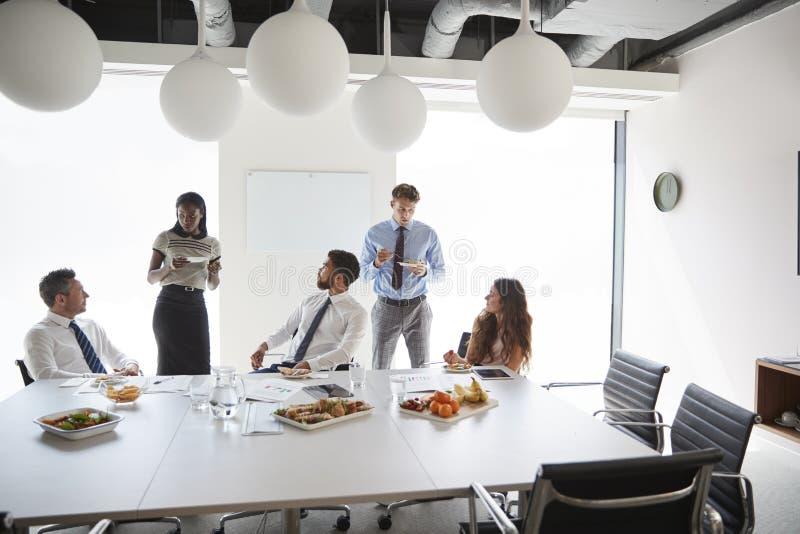 Affärsmän och affärskvinnor som möter i modern styrelse över arbetelunch royaltyfria bilder