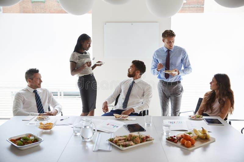 Affärsmän och affärskvinnor som möter i modern styrelse över arbetelunch arkivfoton