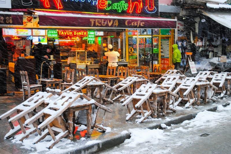 Affärsmän på Istanbul marknadsför att sälja en variation av gods under ett snöfall arkivfoton